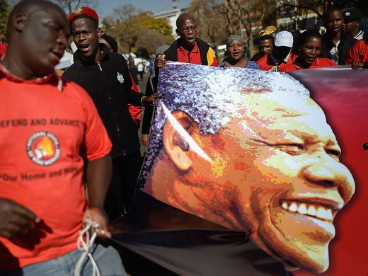 Members of the African National Congress gather outside the Mediclinic Heart Hospital during a rally for former South African president Nelson Mandela on July 4 in Pretoria. Mandela, 94, is being treated for a recurring lung infection at the hospital.