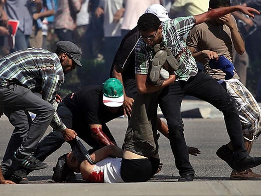 Supporters of ousted Egyptian President Mohammed Morsi rush a wounded man away from the scene of a shooting outside the Egyptian army's Republican Guard headquarters on July 5 in Cairo. At least three Morsi supporters were killed.
