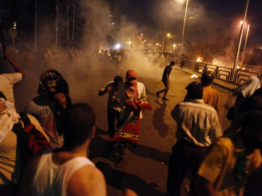 People run for cover as security forces fire tear gas to disperse supporters of ousted Egyptian president Mohammed Morsi outside the Republican Guard headquarters in Cairo in the early hours of July 8.