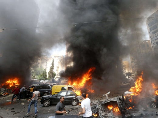 People rush to help at the scene of a car bombing that rocked the Beirut neighborhood of Bir al-Abed on July 9. The area is a stronghold of Lebanon's Shiite Hezbollah movement.