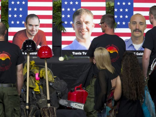 Alumni of the Granite Mountain Hotshots inspect photographs of the 19 fallen firefighters before a memorial service to the group that died June 30 fighting the Yarnell Hills Fire.
