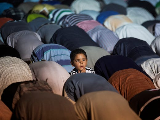 An Egyptian boy prays with supporters of the ousted Egyptian President Mohammed Morsi during Iftar, the evening meal when Muslims break their fast during the Islamic month of Ramadan, in Nasr City, a suburb of Cairo, Egypt, on July 10, 2013.