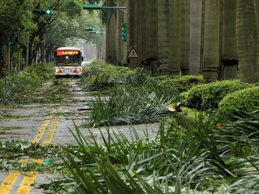 A public bus maneuvers through a path of debris from strong winds of Typhoon Soulik early Saturday on July 13, 2013, in Taipei, Taiwan. The weather system made landfall on Saturday morning, bringing strong winds and up to 14 inches of rain.