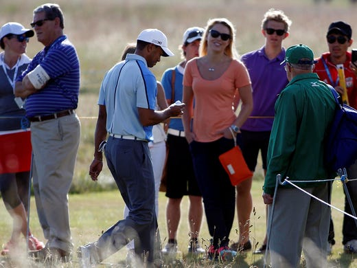 Tiger Woods exits the 12th green as Lindsey Vonn looks on during a practice round for the 2013 The Open Championship at Muirfield Golf Club.