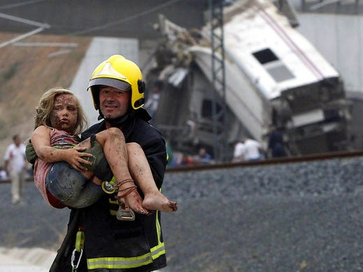 A firefighter carries an injured girl from the scene of a train derailment on July 24 in Santiago de Compostela, Spain. At least 80 people were killed in the country's worst rail disaster in 40 years.