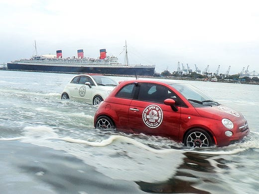 Two of the Fiats, actually personal watercraft, go for a swim with Cunard's original the Queen Mary, now a tourist attraction, in the background in Long Beach, Calif.