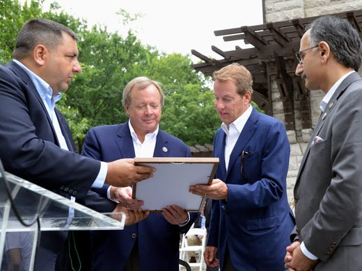 Edsel Ford, second from left, and Bill Ford look over a picture commemorating the 150th birthday of their great-grandfather, Henry Ford