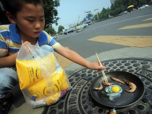 A child cooks shrimp and an egg in a frying pan heated by a manhole cover on a hot summer day on July 31 in Jinan, China. It has been so hot that eggs are hatching without incubators and a highway billboard burst into flames in one of the worst heat waves in 140 years.