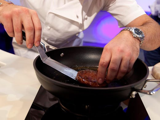 Richard McGeown, a chef at Couch's Great House Restaurant, grills a burger made from cultured beef on Aug. 5 in London. The cultured meat was developed by Mark Post of Maastricht University in the Netherlands.
