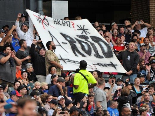 Fans hold up a banner referencing New York Yankees third baseman Alex Rodriguez as he comes up to bat against the Chicago White Sox at US Cellular Field.