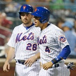 New York Mets Daniel Murphy celebrates with Wilmer Flores after they scored on Kevin Plawecki's fourth-inning, RBI single against the Baltimore Orioles in New York, Tuesday.