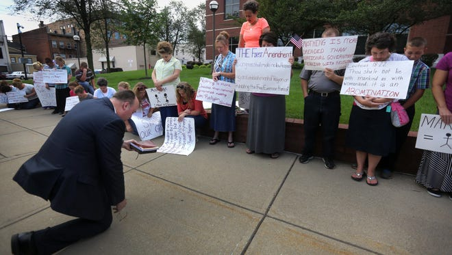 Lee Watts of Lexington leads supporters of Rowan County Clerk Kim Davis in prayer last month outside the federal courthouse in Covington.