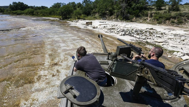 Spencer Jones, left, and his cousin, Casey Jones, right, watch as their family member drives a Sherman Easy 8 tank through a river during an Allies and Axis all-day DriveTanks.com experience at Ox Ranch, Wednesday, May 24, 2017 in Uvalde, Texas.