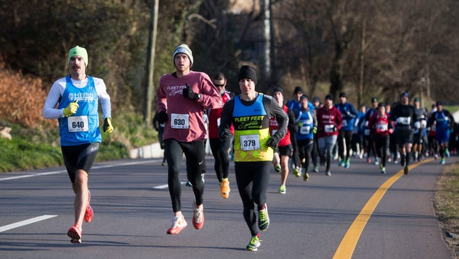 Participants run in Calhoun's New Year's Day 5K run on Neyland Drive Monday, Jan. 1, 2018. Ethan Coffey, of Knoxville, finished first with a time of 15 minutes and 16seconds. Gina Rouse was the first female finisher with a time of 17 minutes and 36 seconds.