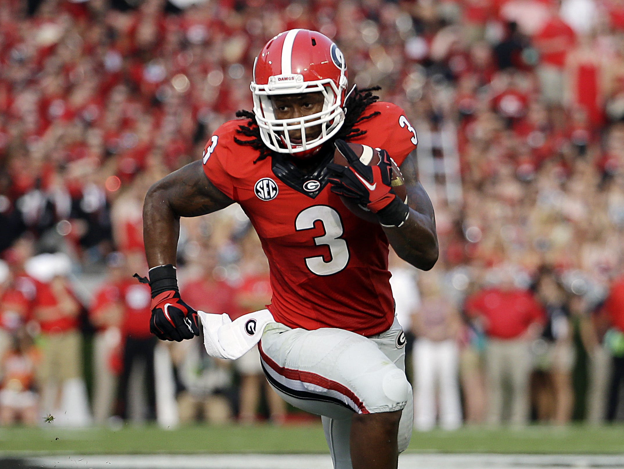 In this Aug. 30, 2014, file photo, Georgia's Todd Gurley runs the ball in the first half of an NCAA college football game against Clemson in Athens, Ga.