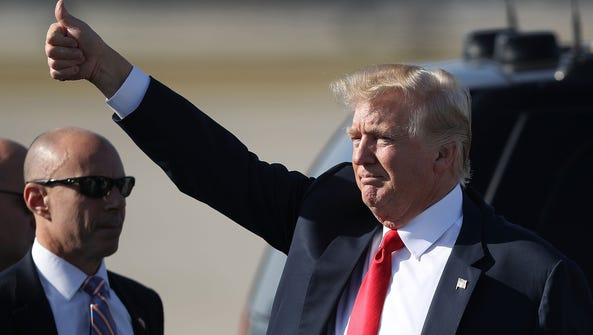 President Trump gives a thumbs up to supporters after