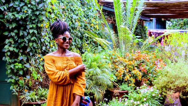 A Black woman standing in a garden.