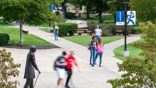 Students visit and walk from classes in front of the Student Union at Washburn University.