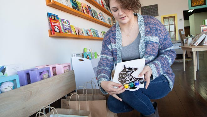 Angie Grau, owner of Paper June, shows the painting kits she started selling this week at her NOTO business Friday. The kits include canvases, a stencil, paint, paint brushes and other items.