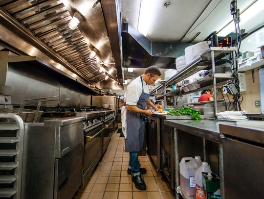 Chef Jason Hanin preps a dish in the kitchen of the