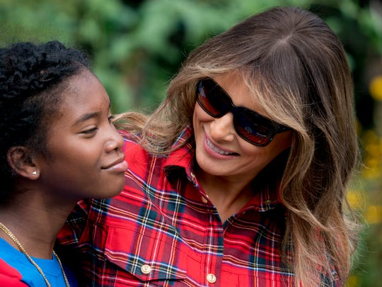 First lady Melania Trump hugs a girl as she participates