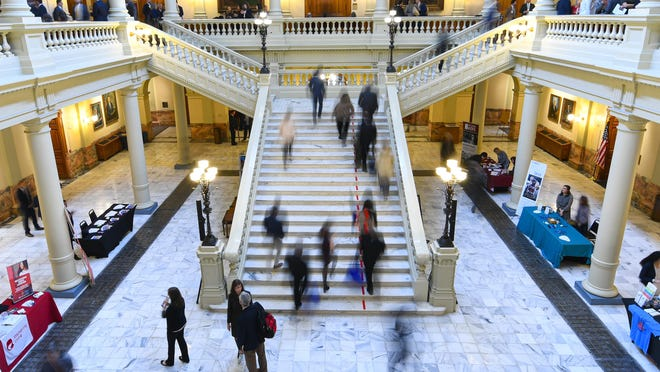 People scurry up Capitol steps as other stand and talk during opening day of the year for the state legislative session, Monday, Jan. 13, 2020 in Atlanta.