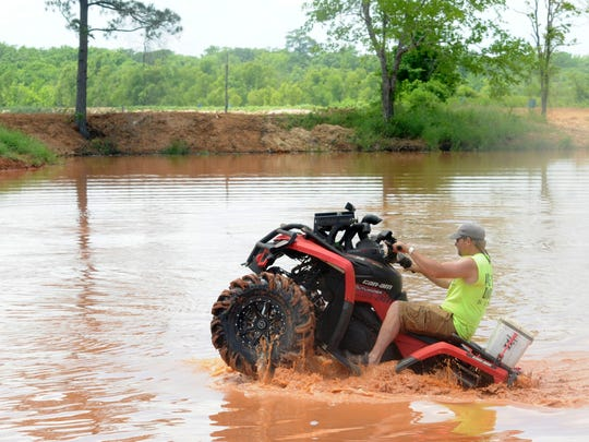In this file photo, a driver rides his ATV in the mud during the opening week of Muddy Bottoms.