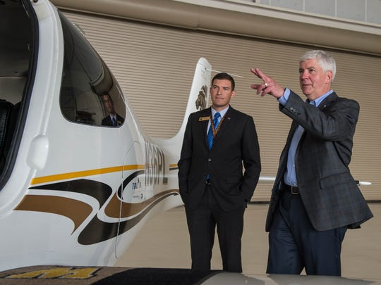 Gov. Rick Snyder and WMU College of Aviation Flight Operations Executive Director Captain Russell Kavalhuna look at a plane during the governor's tour of the Battle Creek campus Thursday.