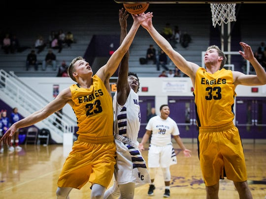Central's Kolby Mallory fights for a rebound past Delta's Carter Anderson and Adam Haynes during their game at the Muncie Fieldhouse Wednesday, Jan. 4, 2017.