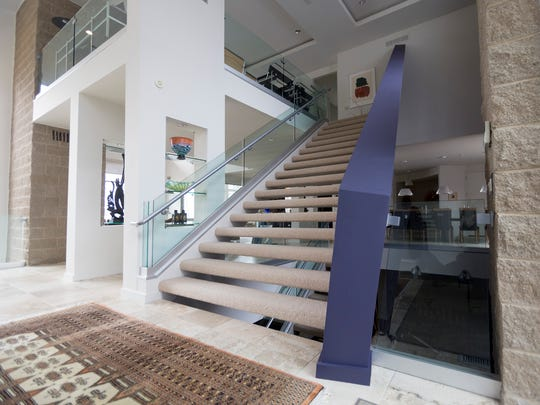 The main staircase is an exclamation point. One side has a half-wall of glass that gives a view of the living room and lake. At the bottom, the stairs are 7-feet wide. As they go up, they narrow and exaggerate the height.
