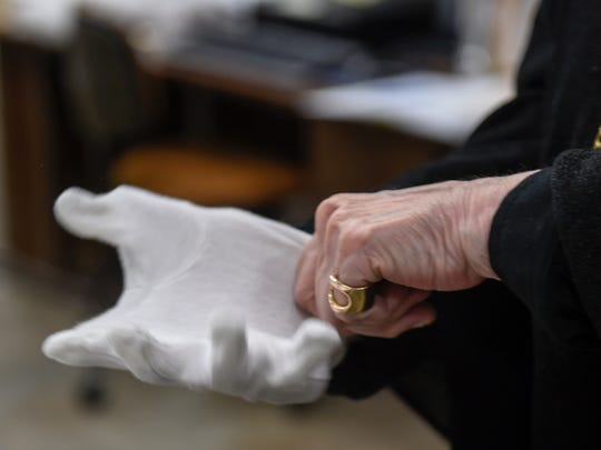Tennessee State Museum Executive Director Lois Riggins-Ezzell puts on gloves to look through exhibits in storage Tuesday, Nov. 15, 2016, in Nashville.