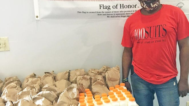 William Toney, president of 100 Suits for 100 Men Williston chapter, with some of the food items the organization has been giving away this summer to children.