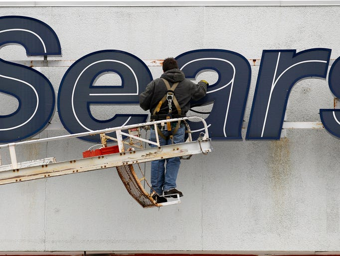 A worker repairs the sign outside the Sears Grand store