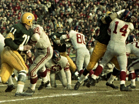 Green Bay Packers defensive end Willie Davis (87) hits New York Giants quarterback Y.A. Tittle (14) in the NFL championship game at new City Stadium on Dec. 31, 1961. At left are Packers linebacker Bill Forester (71) and Giants tackle Greg Larson (53).