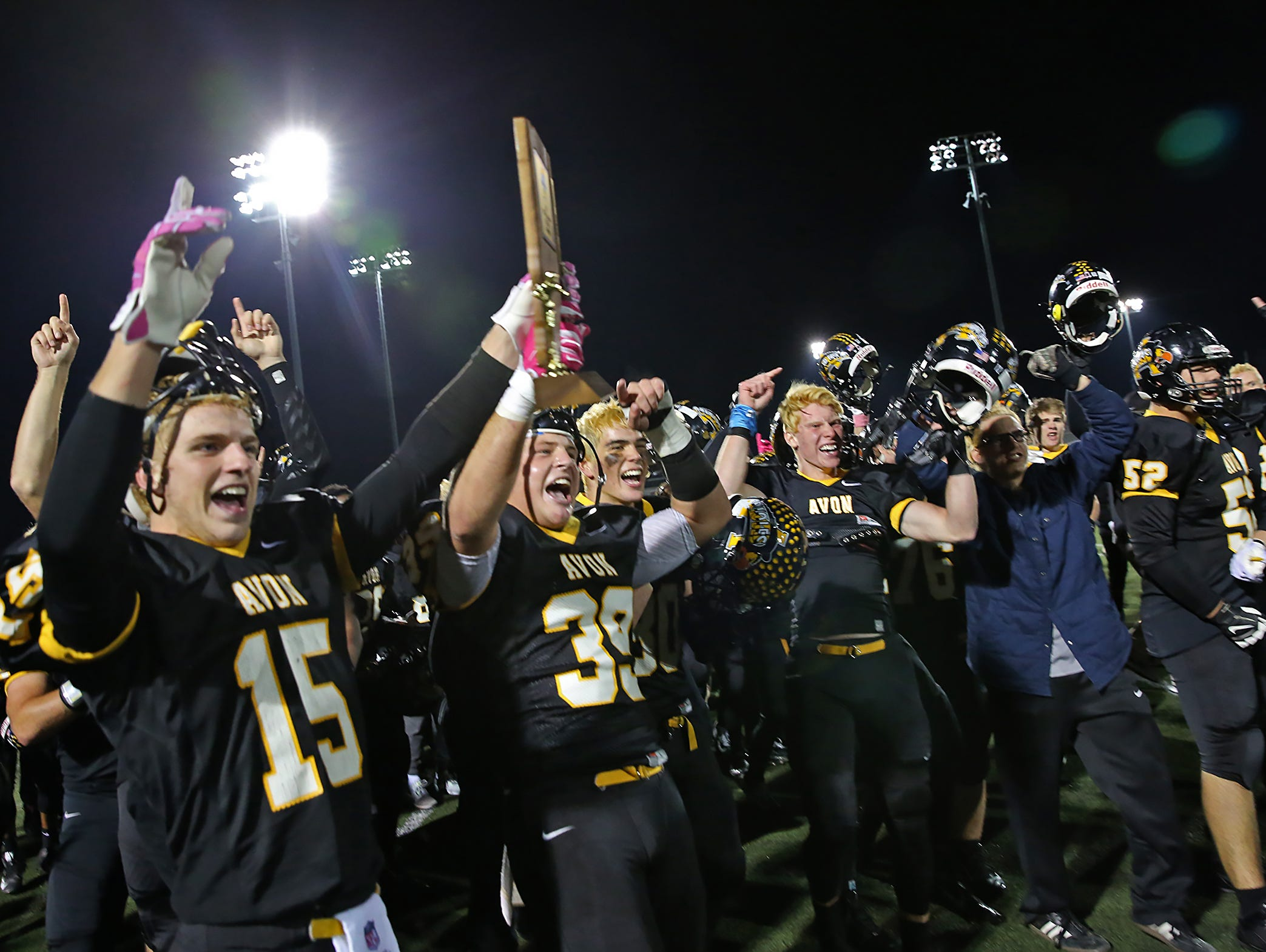 Avon players celebrate the team victory after the Ben Davis at Avon sectional championship, Friday, October 30, 2015. Avon won 27-22.