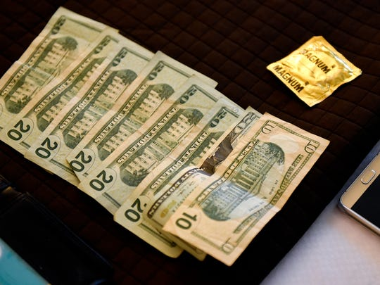 Money and a condom confiscated from a suspected sex buyer are photographed as evidence by members of the Central Minnesota Sex Trafficking Task Force during a June 3, 2016, sting at a St. Cloud hotel.