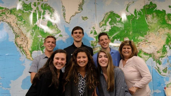 The six Community School of Naples students who traveled to New York to participate in the 40th annual UNIS-UN conference pose for a photo at their school with their history teacher, Sue Herting.