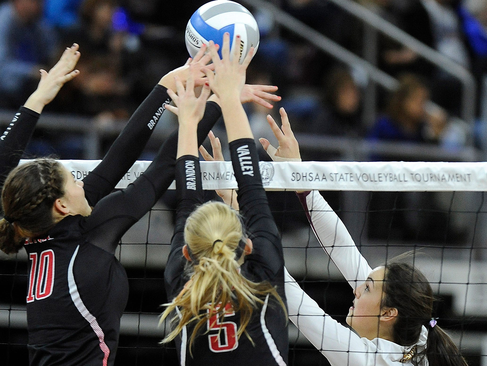 Harrisburg's #3 Samantha Slaughter sets the volleyball against Brandon Valley's #10 Hannah Paauw and #5 Hanna Jellema during state semifinals volleyball action at the Denny Sanford Premier Center in Sioux Falls, S.D., Friday, Nov. 20, 2015.