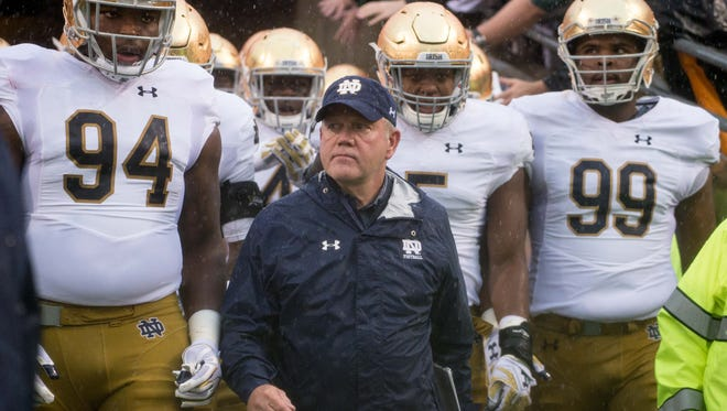 Oct 8, 2016; Raleigh, NC, USA; Notre Dame Fighting Irish head coach Brian Kelly leads his players onto the field for the game against the North Carolina State Wolfpack at Carter-Finley Stadium. Mandatory Credit: Matt Cashore-USA TODAY Sports