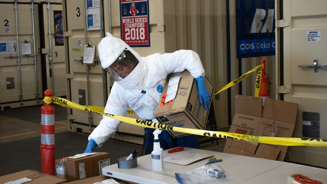 Jade Klinger passes boxes of used N95 masks into a chamber for decontamination on May 14, 2020. Inside each box, masks are double-bagged to reduce the chance of coronavirus exposure during handling.
