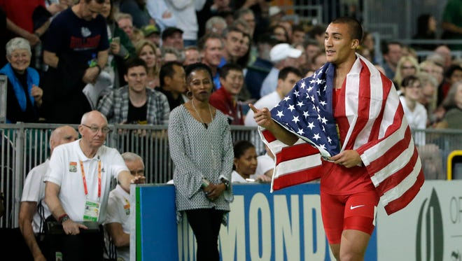 United States' Ashton Eaton walks with the flag after he won the heptathlon during the World Indoor Athletics Championships, Saturday, March 19, 2016, in Portland.