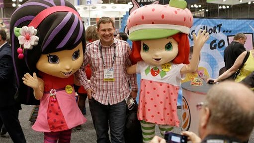 """In  this file photo, characters Strawberry Shortcake, right, and Cherry Jam, left, pose for a photograph with David Yakos at Toy Fair 2014 at the Jacob K. Javits Convention Center  in New York.   Iconix, the brand licensing company that owns the """"Peanuts"""" gang of characters, says it is buying the rights to cartoon character Strawberry Shortcake for $105 million from greeting card company American Greetings."""