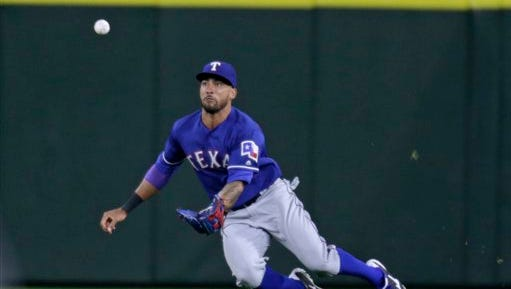 Texas Rangers left fielder Ian Desmond dives for a ball hit by Seattle Mariners' Robinson Cano during a baseball game last week.