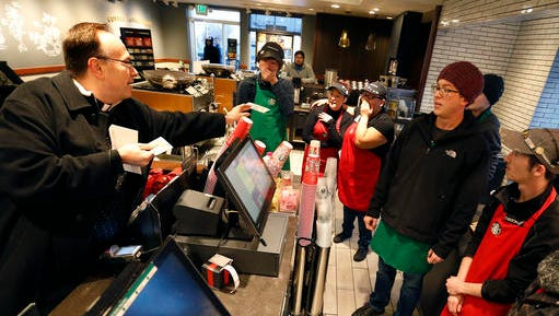 In this Dec. 19, 2016, Father Jim Sichko handed out a $100 bills to employees at a Starbucks in Lexington, Ky. Sichko paid out about $6,000 in holiday good will to a Starbucks counter crew, a Muslim refugee family, a Hispanic family with a desperately ill father and an LGBT man who needed help with groceries for himself and his mother. (Charles Bertram/Lexington Herald-Leader via AP)