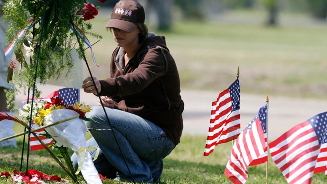 Eva Rowe of Beaumont kneels in front of a flower wreath she placed at a make-shift memorial outside the BP plant in Texas City, Texas, Thursday, March 23, 2006, on the one year anniversary of an explosion that killed 15 people, including her parents, James and Linda Rowe.