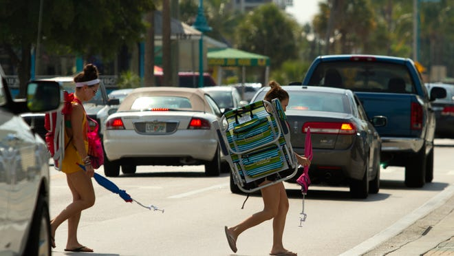 Abby Griswold, of Monson, Mass., and Katie Sassa, of Philadelphia, cross Estero Boulevard in Fort Myers Beach.