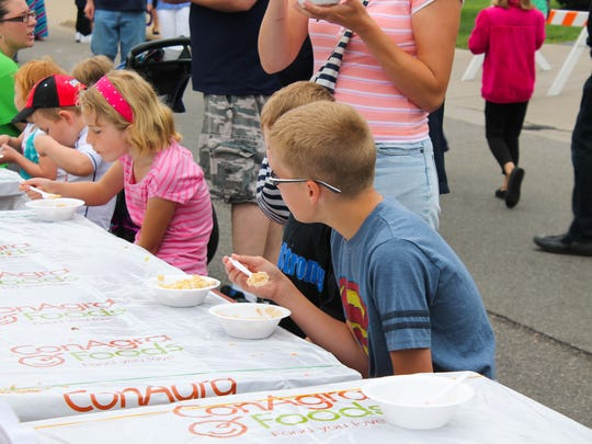 """Kids eat breakfast at the """"World's Longest Breakfast Table"""" at the Cereal Festival in Battle Creek, Mich."""