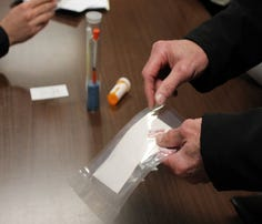 """A Belleville man handles a bag of heroin on display alongside syringes during a """"Coffee with a Cop"""" event the Belleville Police Department held Wednesday, Jan. 18, 2017. Police warned of the dangers of drug abuse following the overdose deaths of two residents in town."""