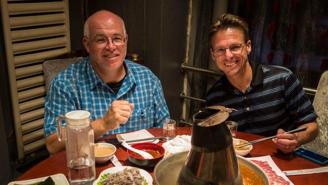 Rodney White (left) and Lynn Hicks enjoy a hot pot meal in Harbin, China, Sept. 4, 2014.