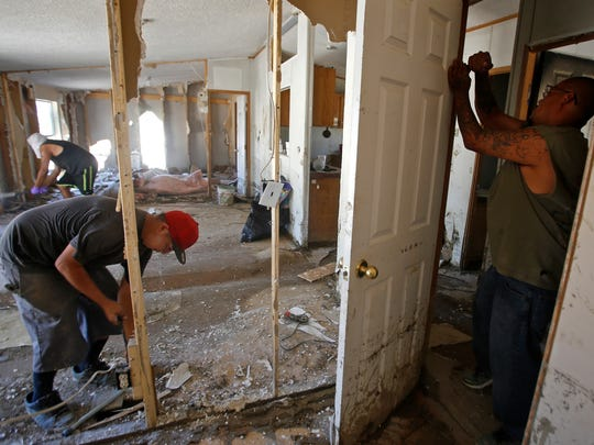 At right, Eric Shorty removes a door on Monday as he and family members help clean up his home on Farm Road in Shiprock.
